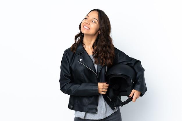Jovem mulher segurando um capacete de motocicleta sobre um fundo branco isolado, pensando em uma ideia