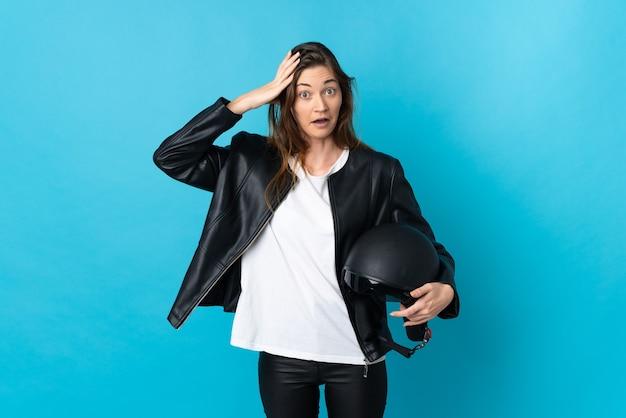 Jovem mulher segurando um capacete de motociclista isolado em uma parede azul com expressão de surpresa