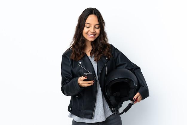 Jovem mulher segurando um capacete de motociclista isolado enviando uma mensagem com o celular