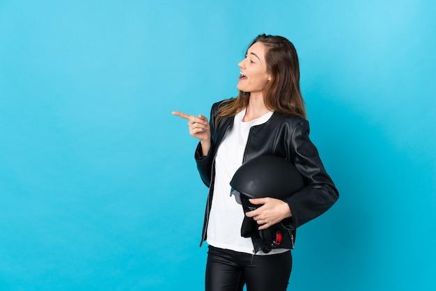 Jovem mulher segurando um capacete de motociclista isolado na parede azul, apontando o dedo para o lado e apresentando um produto