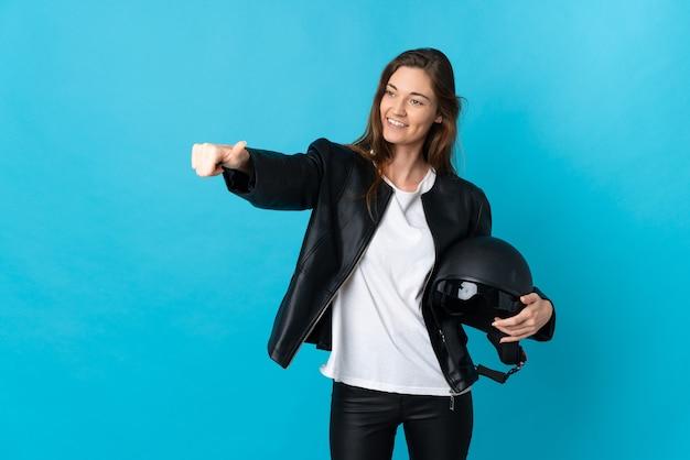 Jovem mulher segurando um capacete de motociclista isolado na parede azul e fazendo um gesto de polegar para cima