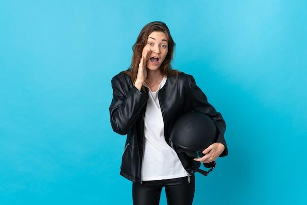 Jovem mulher segurando um capacete de motociclista isolado na parede azul, gritando com a boca aberta