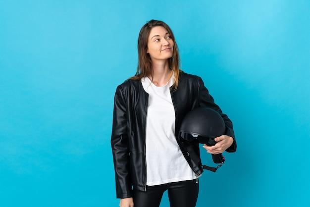 Jovem mulher segurando um capacete de motociclista isolado na parede azul, tendo uma ideia enquanto olha para cima