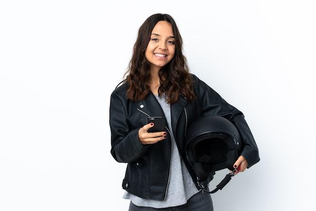 Jovem mulher segurando um capacete de motociclista sobre um branco isolado enviando uma mensagem com o celular