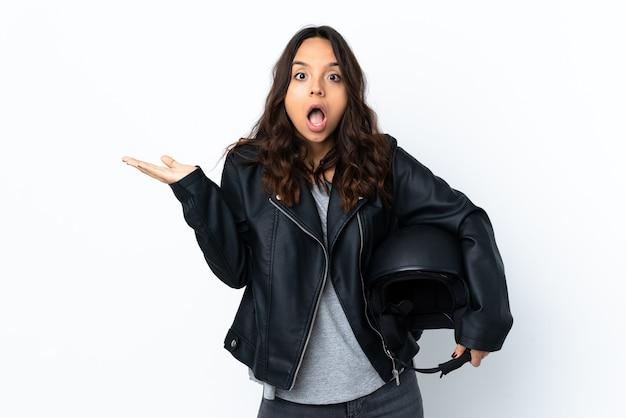 Jovem mulher segurando um capacete de motociclista sobre um fundo branco isolado, fazendo gestos de telefone e duvidando