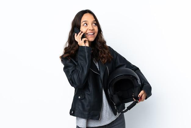 Jovem mulher segurando um capacete de motociclista sobre um fundo branco isolado segurando um café para levar e um móbile