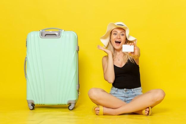Jovem mulher segurando um cartão branco de frente
