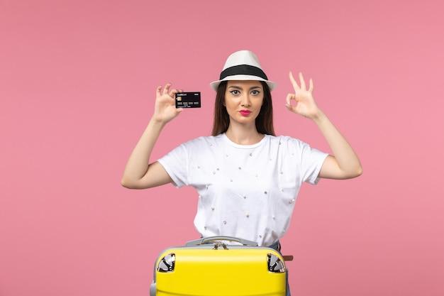 Jovem mulher segurando um cartão de banco preto em uma viagem de cor rosa