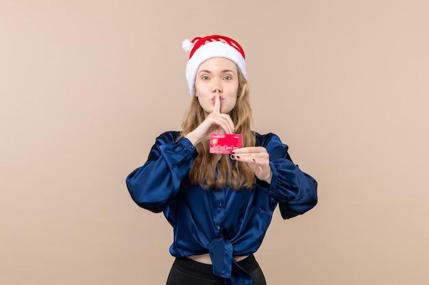 Jovem mulher segurando um cartão de banco vermelho em uma foto de férias de fundo rosa, ano novo, natal, dinheiro, vista frontal