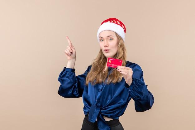 Jovem mulher segurando um cartão de banco vermelho na foto de férias fundo rosa, ano novo, natal, dinheiro, vista frontal