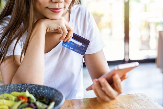 Jovem mulher segurando um cartão de crédito e um smartphone