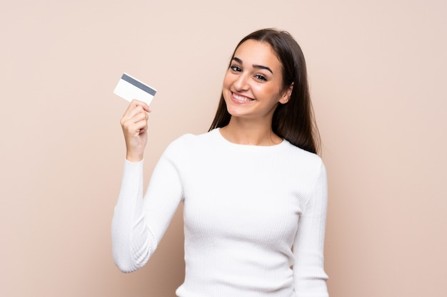 Jovem mulher segurando um cartão de crédito