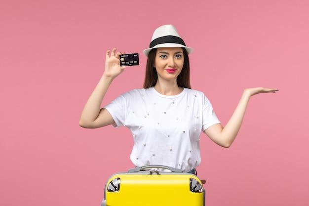 Jovem mulher segurando um cartão preto do banco em uma viagem de cor rosa na mesa de trabalho no verão