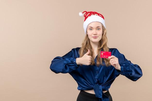Jovem mulher segurando um cartão vermelho no fundo rosa dinheiro férias foto ano novo natal emoção lugar livre
