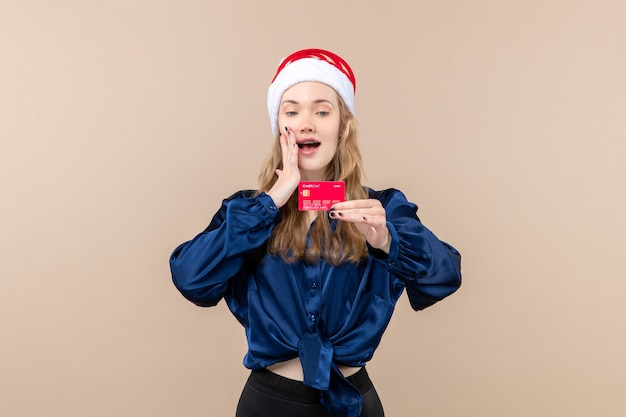 Jovem mulher segurando um cartão vermelho no fundo rosa foto de férias ano novo emoção natal dinheiro