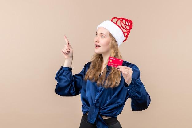 Jovem mulher segurando um cartão vermelho no fundo rosa, foto de férias, ano novo, natal, dinheiro, emoções