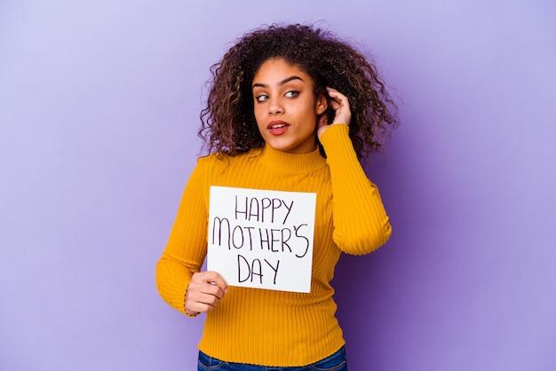 Jovem mulher segurando um cartaz do dia das mães feliz isolada tentando ouvir uma fofoca