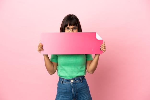 Jovem mulher segurando um cartaz vazio e se escondendo atrás dele