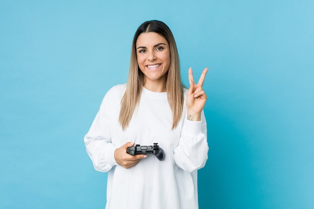 Jovem mulher segurando um controlador de jogo, mostrando o número dois com os dedos.