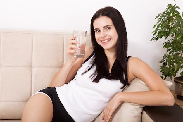 Jovem mulher segurando um copo d'água em casa.
