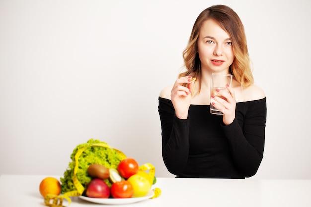Jovem mulher segurando um copo de água e um comprimido para perda de peso