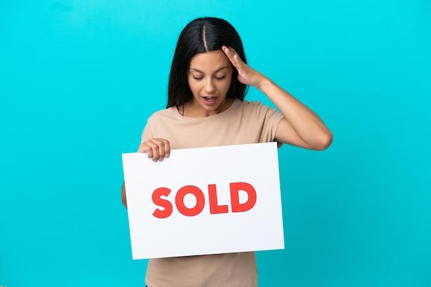 Jovem mulher segurando um fundo isolado segurando um cartaz com o texto vendido com expressão de surpresa