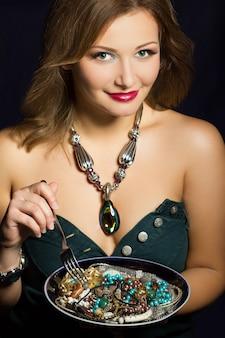 Jovem mulher segurando um garfo e prato com joias