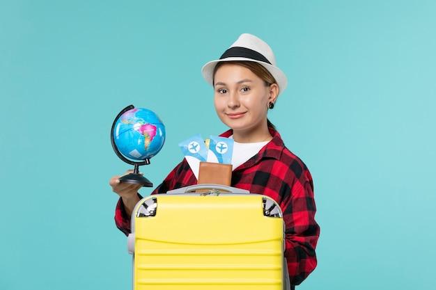 Jovem mulher segurando um globo e ingressos no espaço azul de frente
