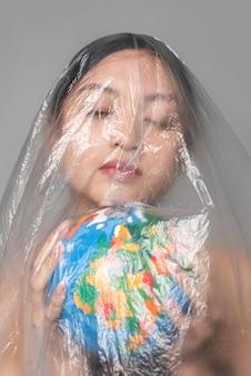 Jovem mulher segurando um globo terrestre enquanto é coberta de plástico
