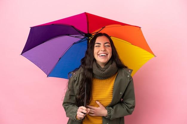 Jovem mulher segurando um guarda-chuva isolado em um fundo rosa e sorrindo muito