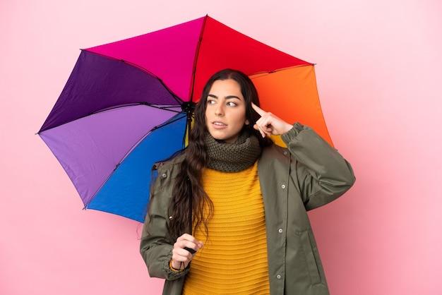 Jovem mulher segurando um guarda-chuva isolado em um fundo rosa, tendo dúvidas e pensando