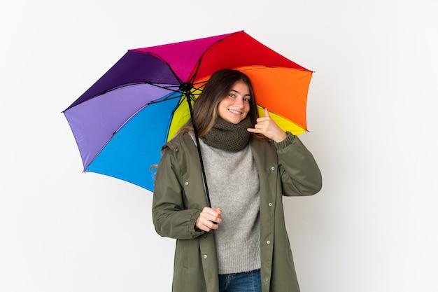 Jovem mulher segurando um guarda-chuva isolado na parede branca, fazendo gesto de telefone. ligue-me de volta sinal