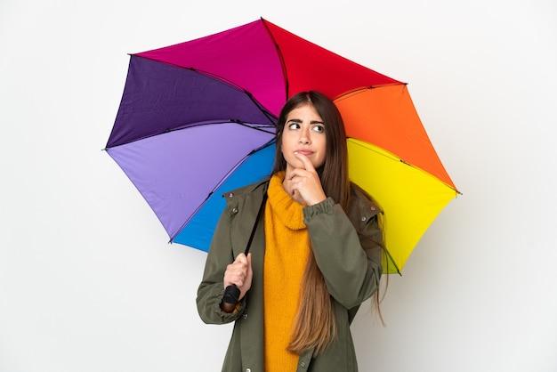 Jovem mulher segurando um guarda-chuva isolado no fundo branco, tendo dúvidas enquanto olha para cima