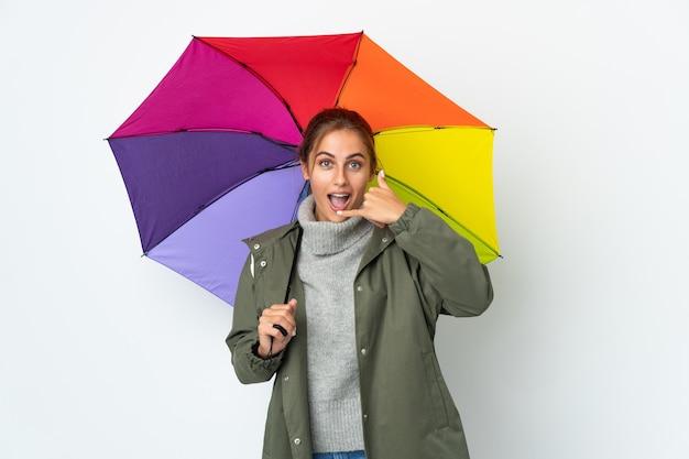 Jovem mulher segurando um guarda-chuva posando isolada contra a parede em branco