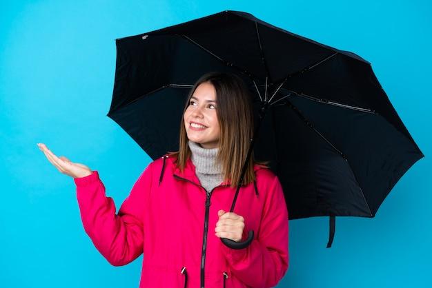 Jovem mulher segurando um guarda-chuva sobre parede azul isolada