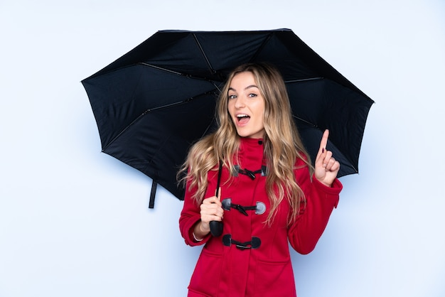 Jovem mulher segurando um guarda-chuva sobre parede isolada