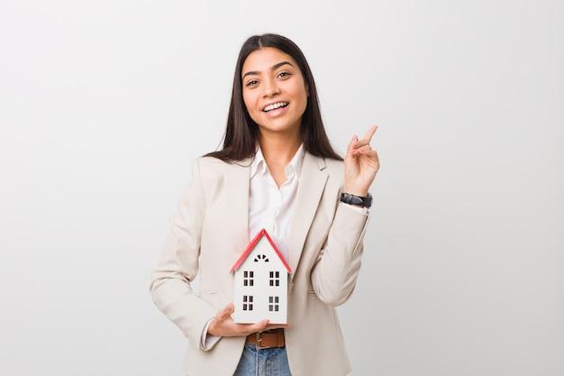 Jovem mulher segurando um ícone de casa sorrindo alegremente apontando com o dedo indicador fora.