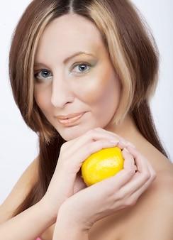Jovem mulher segurando um limão