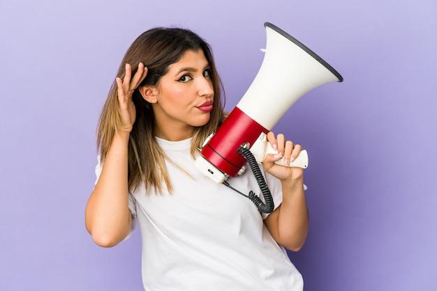 Jovem mulher segurando um megafone isolado tentando ouvir uma fofoca