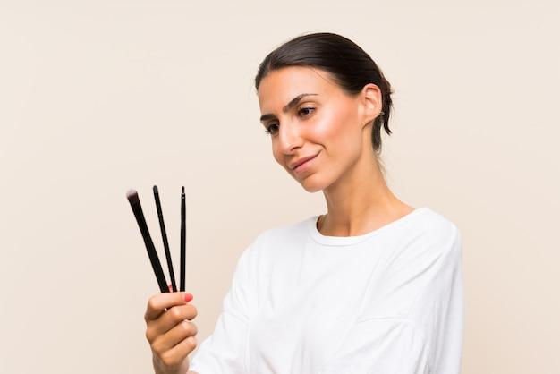 Jovem mulher segurando um monte de pincel de maquiagem