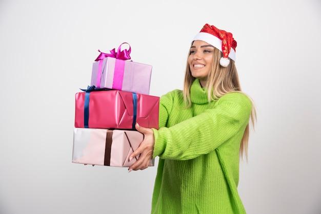 Jovem mulher segurando um monte de presentes de natal festivos.