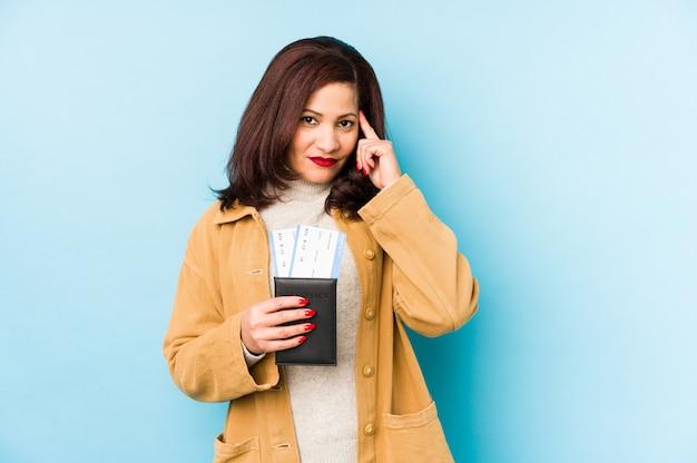 Jovem mulher segurando um passaporte isolado apontando o templo com o dedo, pensando, focado em uma tarefa