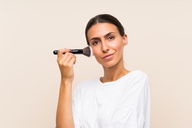 Jovem mulher segurando um pincel de maquiagem