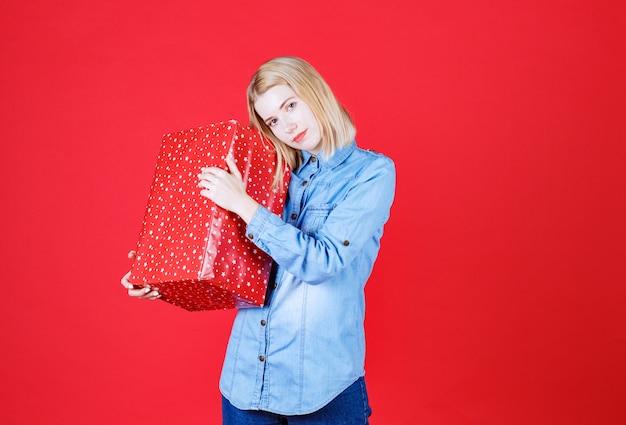 Jovem mulher segurando um presente de aniversário em uma parede vermelha
