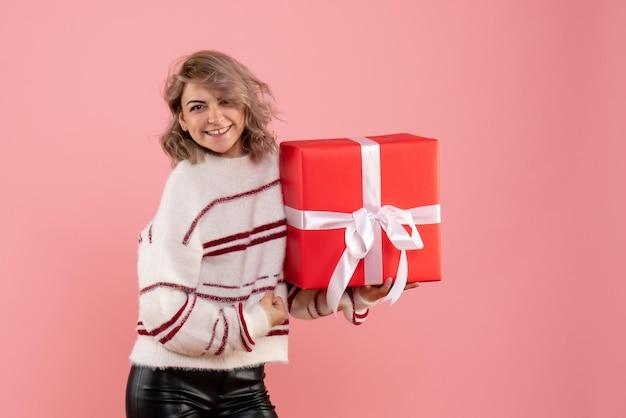 Jovem mulher segurando um presente de natal de frente