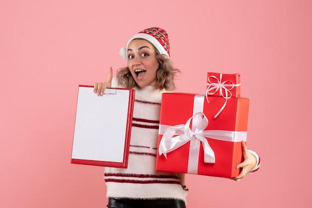 Jovem mulher segurando um presente de natal e uma nota frontal