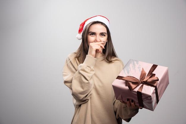 Jovem mulher segurando um presente de natal sobre um fundo cinza.