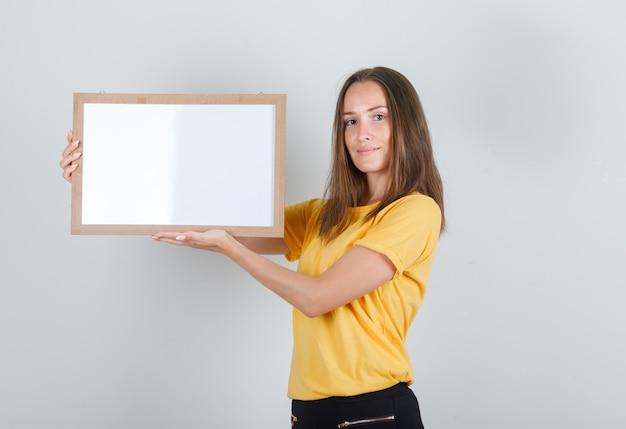 Jovem mulher segurando um quadro branco e sorrindo com uma camiseta amarela
