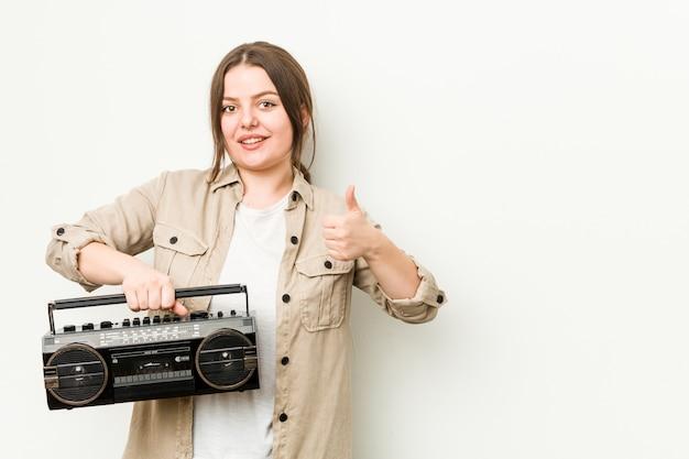 Jovem mulher segurando um rádio retrô, sorrindo e levantando o polegar