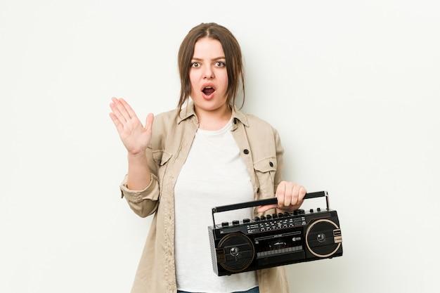 Jovem mulher segurando um rádio retrô surpreso e chocado.